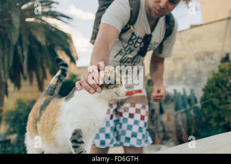 Young Man Caressing Calico Cat - Stock Photo