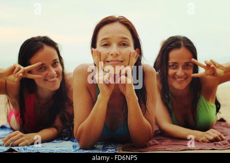 Portrait Of Happy Friends Making Peace Sign On Beach - Stock Photo