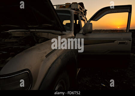 Toyota Land Cruiser with open door and hood in the Danakil depression at sunset, Afar Region, Ethiopia - Stock Photo