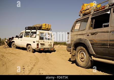 Men pushing a Toyota stuck in the sand in the Danakil depression, Afar Region, Ethiopia - Stock Photo