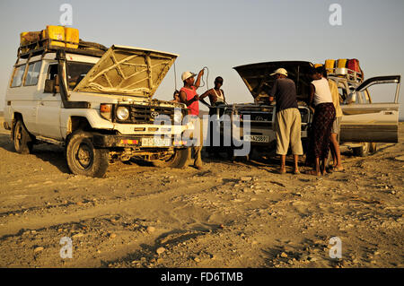Men using jumper cables between two off-road vehicles in the Danakil desert, Afar Region, Ethiopia - Stock Photo