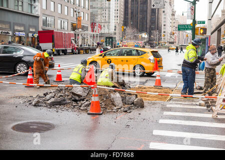 Public workers digging a hole on the street of New York City to perform repair - roped off to secure the area - Stock Photo