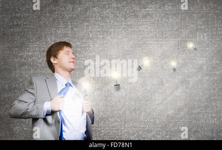 Young businessman opening chest and acting like super hero - Stock Photo