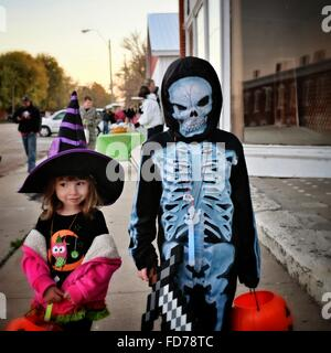 Person In Monster Costume Standing By Cute Girl On Footpath During Halloween - Stock Photo