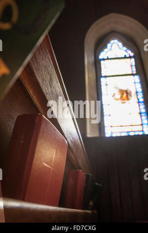 Christian bible in pews with stained glass window - Stock Photo