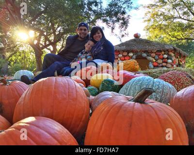 Portrait Of Smiling Family With Pumpkins At Village - Stock Photo