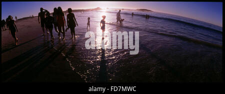 People Walking Along Sandy Beach Silhouetted Against Sunlight - Stock Photo