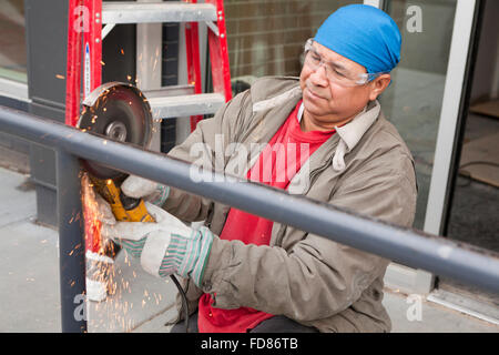 Construction worker cutting steel pipe with angle grinder tool - USA - Stock Photo