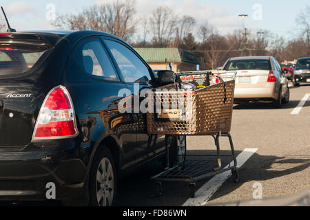 Grocery shopping cart leaning on parked car - USA - Stock Photo
