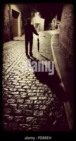 Rear View Of Man With Umbrella Standing On Street At Night - Stock Photo
