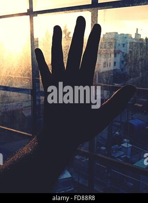 Close-Up Of Silhouette Hand On Window Against Cityscape - Stock Photo