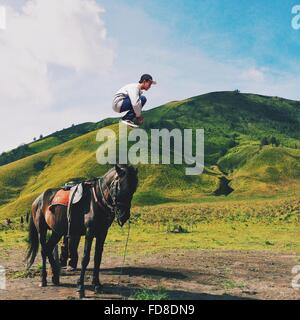Side View Of Man Jumping In Mid Air Against Green Mountains - Stock Photo