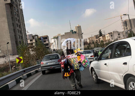 Afghan selling objects in middle of heavy traffic in Tehran, Iran. - Stock Photo