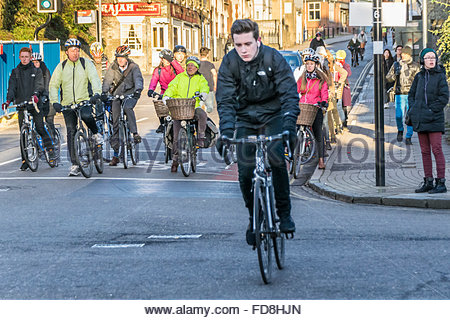 A lone cyclist makes a break for it as other cyclists wait at the traffic lights in the morning on Bridge Street, - Stock Photo