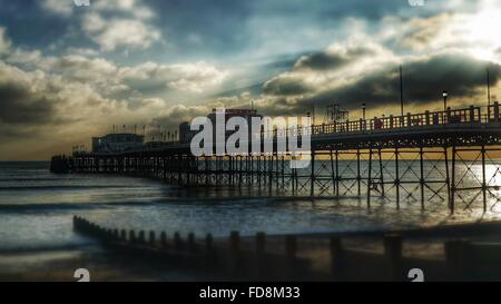 Low Angle View Of Worthing Pier Over Sea Against Cloudy Sky During Sunset - Stock Photo