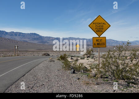 Flash flood warning signs aon the roadside in Death Valley California warning visitors of potential flooding danger - Stock Photo