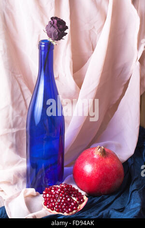Still Life with pomegranate, bottle and dry rose - Stock Photo