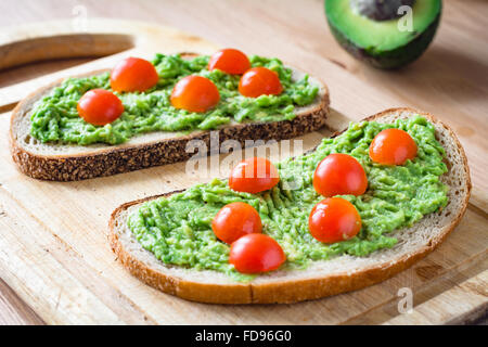 Guacamole and bread. Toast with avocado and cherry tomatoes on wooden cutting board - Stock Photo