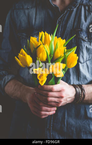 Man holding yellow tulips. Gift card template, poster or greeting card - man holding bouquet of yellow tulips for - Stock Photo