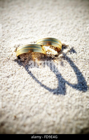 High Angle View Of Wedding Rings On Sand - Stock Photo