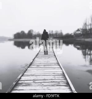Full Length Rear View Of Woman Standing On Pier - Stock Photo