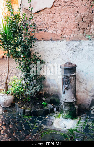 One of the classic Roman water fountains ('Fontanella' or 'Nasone') located throughout the city of Rome, Italy - Stock Photo