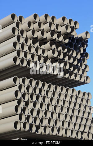 close-up of grey, plastic water pipes stacked in an outdoor yard for storage and delivery - Stock Photo