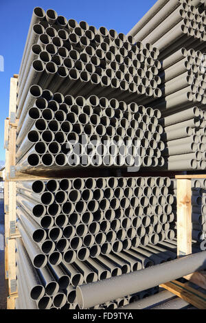 close-up of grey, plastic water pipes stacked in metal frames an outdoor yard for storage and transport - Stock Photo
