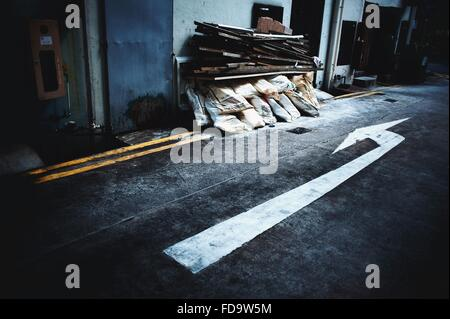 Arrow Sign On Road Pointing At Stack Of Sacks - Stock Photo