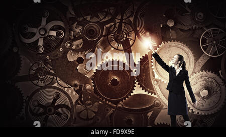 Young businesswoman reaching hand to touch gears mechanism - Stock Photo