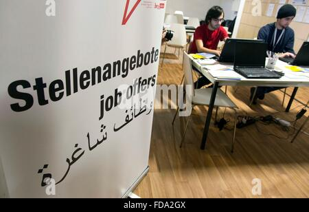 Refugees from Syria look at job offers at a new job center for migrants and refugees at former Tempelhof Airport - Stock Photo