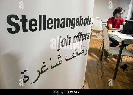 A refugee from Syria look at job offers at a new job center for migrants and refugees at former Tempelhof Airport - Stock Photo