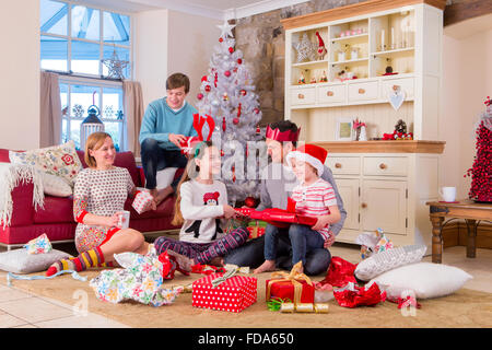 Two Generation Family opening presents at christmas time. They are looking at each other and wearing christmas clothing. - Stock Photo