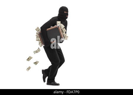 Studio shot of a male burglar with a mask on his head running with a briefcase full of money isolated on white background - Stock Photo