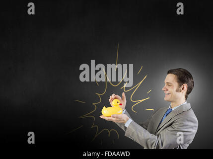 Funny businessman with yellow rubber duck toy - Stock Photo