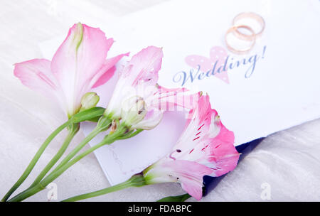 Beautiful pink lilies rest on top of a wedding invitation with the wedding rings out of focus in the background. - Stock Photo