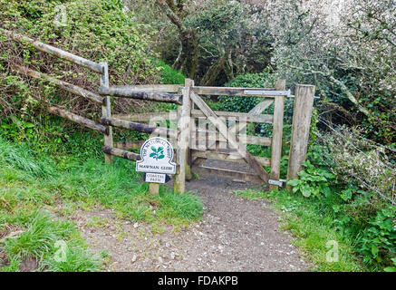 National Trust omega sign saying Mawnan Glebe on a footpath and gate at  Cornwall England UK - Stock Photo