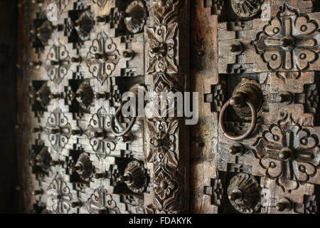 full frame close up of a heavily carved engraved wood wooden front doors with circular door handles pulls in India - Stock Photo