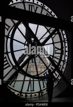 a silhouette figure standing looking through a huge clock face window onto the Paris scene outside, Musee D'Orsay - Stock Photo