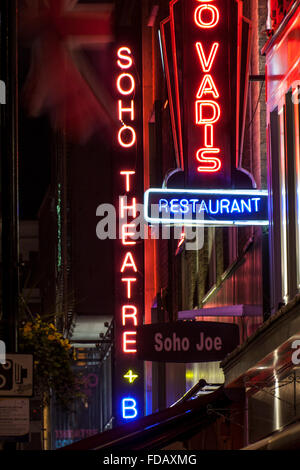 Soho Theatre neon sign at night with other signage Soho street scene nightlife Dean Street Soho London England UK - Stock Photo