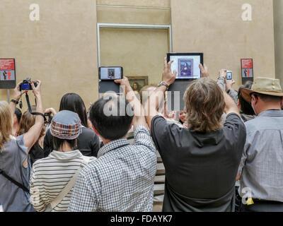 PARIS, FRANCE - AUGUST 28 2013: - A crowd of visitors taking pictures of Leonardo Da Vinci's famous portrait of - Stock Photo