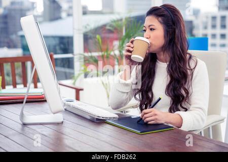 Asian woman drinking and using digital board while looking at computer monitor - Stock Photo
