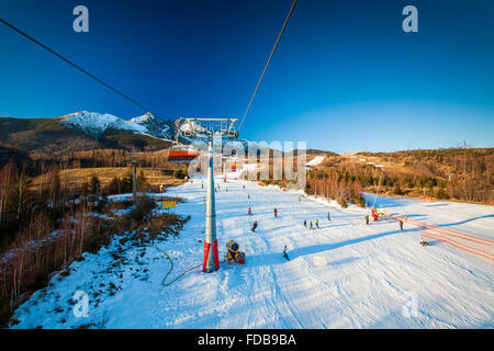 TATRANSKA LOMNICA, SLOVAKIA, 23 DEC 2015: Cable car at a popular ski resort in Tatranska Lomnica, High Tatras, with - Stock Photo