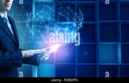 Hands of businessman with tablet pc against high tech background - Stock Photo