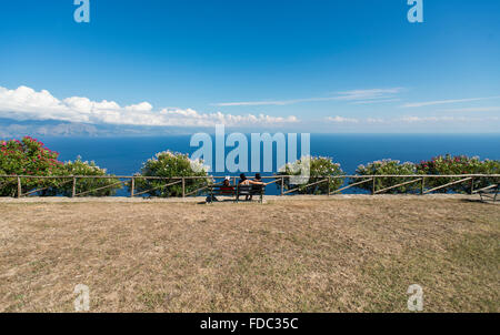 Three young women on a bench overlooking the Mediterranean Sea on the Gulf of Policastro on a lookout, Cilento,Campania,Italy - Stock Photo