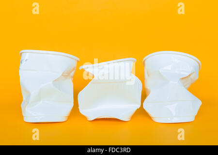 Waste plastic cup on a yellow background. - Stock Photo
