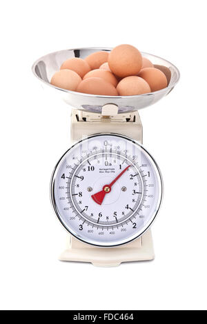 Kitchen Scales with fresh eggs on white background - Stock Photo