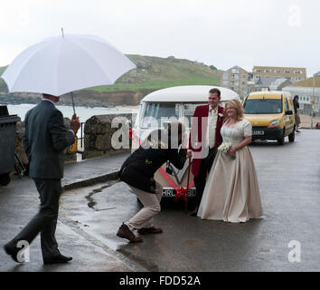 Bride and groom photographed in front of an Vintage Volkswagen VW Bus ca. 1965 oa a rainy day in St. Ives Cornwall - Stock Photo