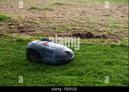 Robot mower on grass England UK Europe - Stock Photo