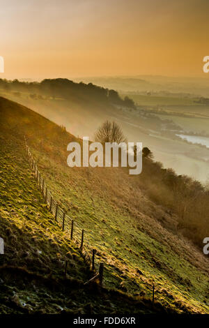 Hillside slopes,mist & sunset over Wiltshire countryside near the town of Westbury from Bratton Camp and  Westbury - Stock Photo